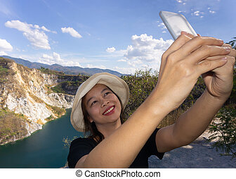 Asian female tourists are taking pictures of themselves at...