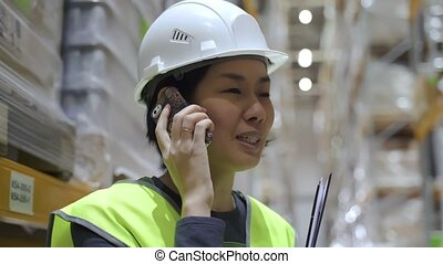 asian female warehouse worker with smartphone. employee talking discussing on the phone
