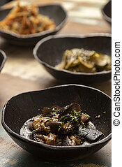 asian fermented kimchi fermented food eggplant on a black bowl and other ingredients on background