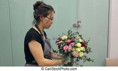 Asian Florist holding a bouquet of red, pink and white roses and berries.