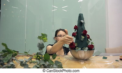 Asian florist prepares roses for a bouquet of green sponge.