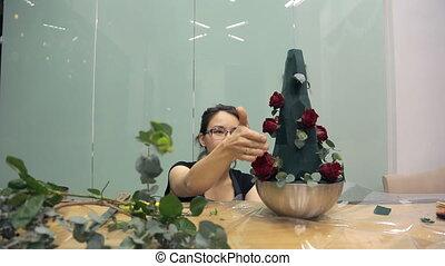 Asian florist prepares roses for a bouquet of green sponge.