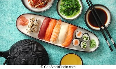 Various sushi rolls placed on ceramic plates. Traditional iron tea pot and green tea in cup. Kimchi and goma wakame salads. Soy souce and chopsticks on sides. Blue background with copy space.