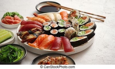 Various sushi rolls placed on round ceramic plate - Asian...