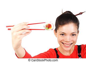Asian food - Beautiful woman holding a tuna maki sushi. ...