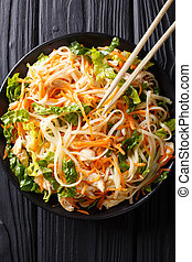 Asian food: chicken salad with rice noodles, carrots and ...