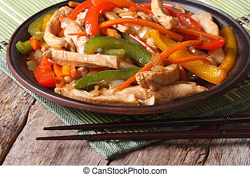 chicken with vegetables close-up and chopsticks on the wooden ta