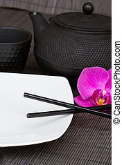 asian food - empty plate with chopsticks and iron tea set