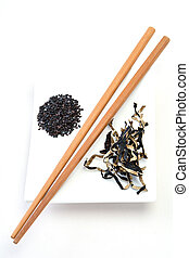 Asian food ingredients such as organic black rice, dried mushrooms with chopsticks