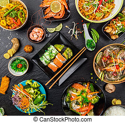 Asian food served on black stone, top view. Chinese and...