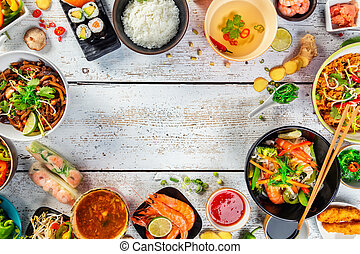 Asian food served on wooden table, top view, space for text...