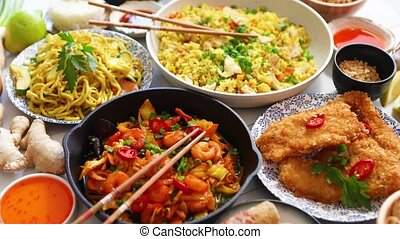 Asian food served. Plates, pans and bowls full of noodles ...