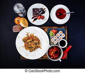 Asian food set. Fried noodles with chicken, miso soup, sushi with salmon, cup of tea and cake.
