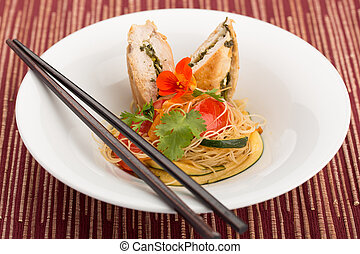 Asian food with piece of stuffed chicken, noodles, zucchini...