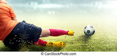 Asian football player woman in orange jersey sliding tackle the ball