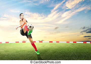 Asian football player woman kicking the ball