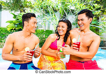 Asian friends drinking cocktails at pool