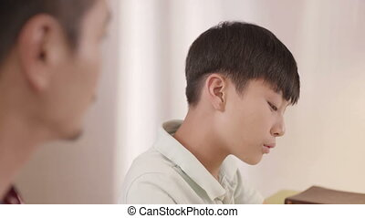 Asian frustrated teenage boy blurring to his father at home