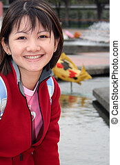 A sweet-looking young asian woman in the park.