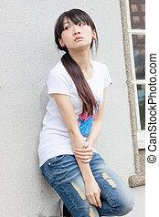 Asian girl against wall