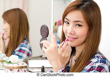 Asian girl applying lipstick