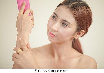 asian girl applying moisturizer - young beautiful asian girl...