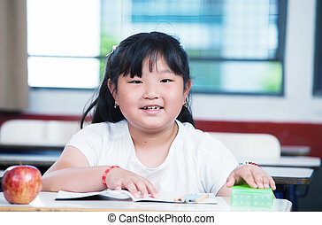 Asian girl at primary school classroom desk.