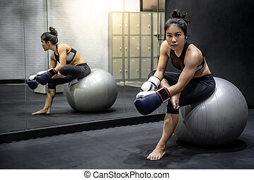 Asian girl boxer sitting on exercise ball in gym
