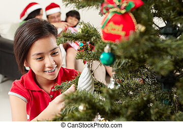 Asian girl decorating Christmas tree