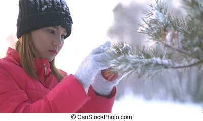 Asian Girl decorating Christmas tree in forest