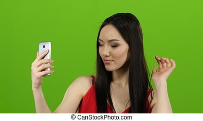 Asian girl does selfie, she smiles while looking at the camera. Green screen