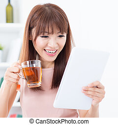 Asian girl drinking tea while using tablet