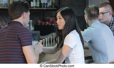 Asian girl drinks red wine while man drinks whiskey