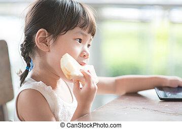 Asian girl eating bread