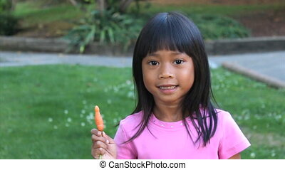 Asian Girl Eating Homegrown Carrot - A cute Asian girl...