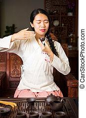 Asian girl enjoying a cup of tea at home