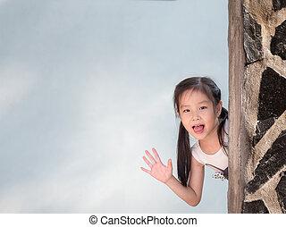 Asian girl hiding behind the wall, peekaboo action