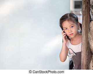 Asian girl hiding behind the wall, use the smart phone