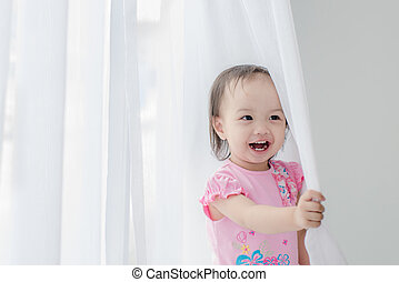 Asian girl holding white curtain at home.