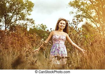 Asian girl in dress in field