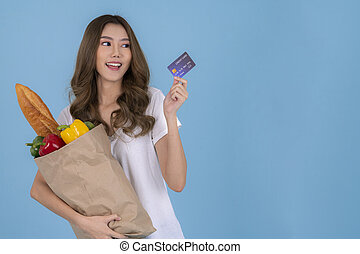 Asian girl in islated background with shopping bag from market and credit card
