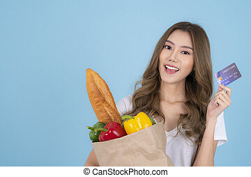 Asian girl in isolated background with shopping bag from market and credit card
