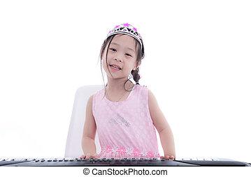 Asian girl in princess dress playing keyboard on white.