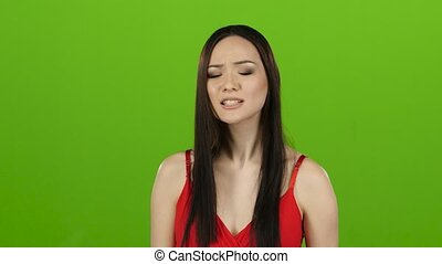 Asian girl is indignant with people, she is angry. Green screen