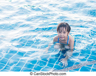 Asian girl is playing in the pool, laying down