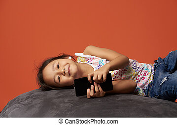 Asian girl lay on sofa with smartphone