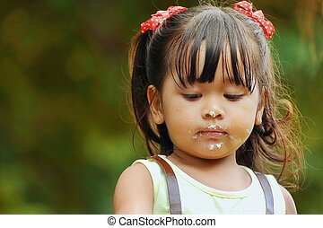 Little asian girl was playing happily in the park, Candy dots on mouth