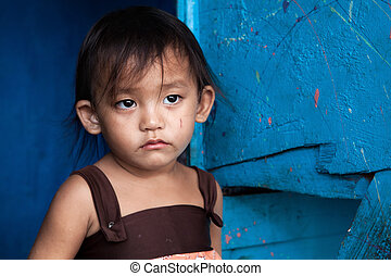 Young Asian girl from poverty stricken area in Manila, Philippines.