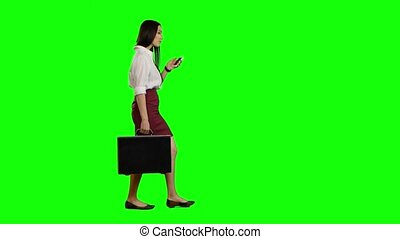 Asian girl looks on the phone and runs. Green screen - Girl...