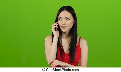 Asian girl looks on the phone, gossiping with her girlfriend. Green screen